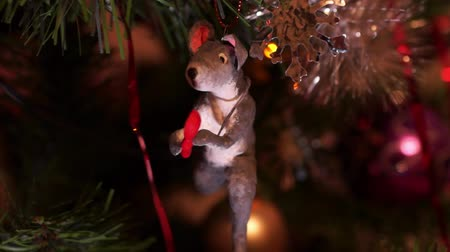 New Years composition, Christmas decorations. Christmas toy of a gray rat hangs on a decorated Christmas tree on the background of a blinking garland. Macro video Wideo