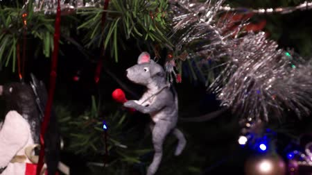 New Years composition, Christmas decorations. Christmas toy of a gray rat hangs on a decorated Christmas tree on the background of a blinking garland. Camera movement from defocus to focus