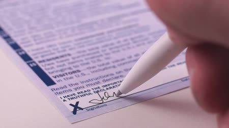 Man fills Customs Declaration Form, puts a signature. Close-up