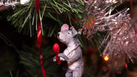kerstpakket : New Years composition, Christmas decorations. Christmas toy of a gray rat hangs on a decorated Christmas tree on the background of a blinking garland. Close-up Stockvideo