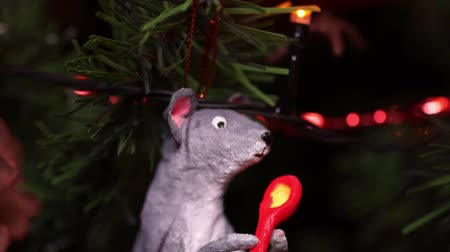 New Years composition, Christmas decorations. Christmas toy of a gray rat hangs on a decorated Christmas tree on the background of a blinking garland. Macro video Stock Footage