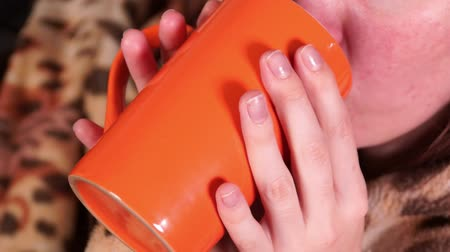 Young red-haired girl, wrapped in a plaid, drinks a drink from an orange color mug. Close-up