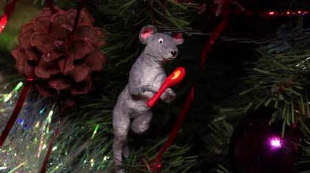 prase : New Years composition, Christmas decorations. Christmas toy of a gray rat hangs on a decorated Christmas tree on the background of a blinking garland. Close-up Dostupné videozáznamy