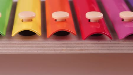 Children xylophone painted with rainbow colors on a white background. Macro video