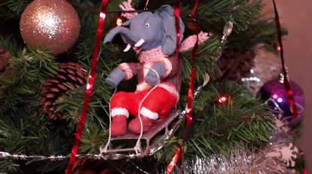 New Years composition, Christmas decorations. Christmas toy elephant on a sledding hangs on a decorated Christmas tree on the background of a blinking garland and other toys. Close-up