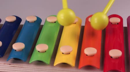 A child plays on a children xylophone painted with rainbow colors on a white background. Close-up