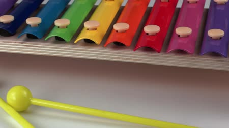 Children xylophone painted with rainbow colors on a white background. Close-up Stock Footage