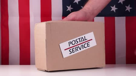 хрупкий : Human sticks a label postal service on parcel on a American flag background. Close-up