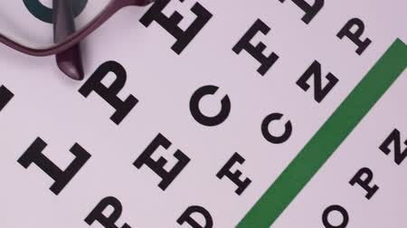 Corrective glasses on the background of the Snellen vision test chart. Close-up