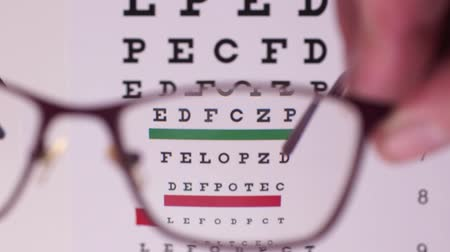 abeceda : Corrective glasses on the background of the Snellen vision test chart. Camera focus through glasses lens