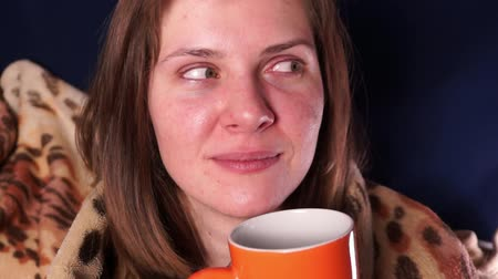 Young beautiful red-haired girl, wrapped in a plaid and with an orange mug in her hands, looks around and looks into the mug. Shows different emotions