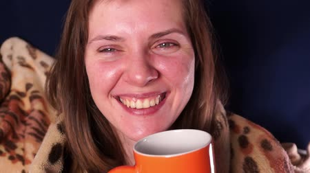 Young beautiful red-haired girl, wrapped in a plaid and with an orange mug in her hands, makes faces and laughs Stock Footage