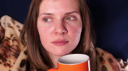 Young beautiful red-haired girl, wrapped in a plaid and with an orange mug in her hands, listens and have a fright Stock Footage