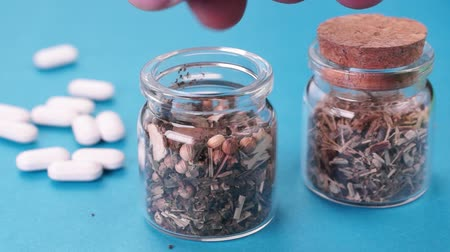 homeopathic : Healer spread on the medicinal powder into a glass jar and closes the cork on the background of another jar and white tablets