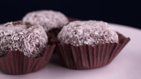 Rum chocolate cakes in coconut flakes rotate on a white plate. Close-up Wideo