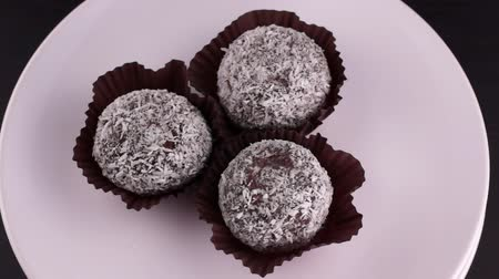 домовой : Rum chocolate cakes in coconut flakes rotate on a white plate. Flat lay Стоковые видеозаписи