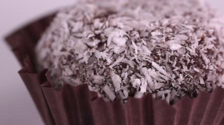 brownie de chocolate : El pastel de chocolate con ron en hojuelas de coco gira sobre un plato blanco. Video macro Archivo de Video