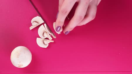 trimmings : Cooking eat. Woman cuts the mushrooms on a pink board. Flat view Stock Footage