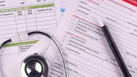 biztosítás : Health insurance claim form, stethoscope and pen lie on top of other medical forms. Close-up Stock mozgókép