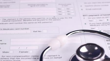 compensar : Medicare claim form, stethoscope and pen lie on top of other medical forms. Close-up