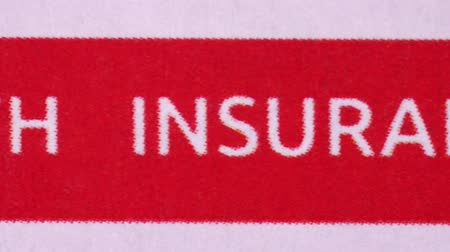 compensar : Words lettering Health insurance claim form printed on a red stripe. Macro video