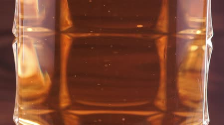 brew : Gas bubbles move in a light beer. Beer poured into a transparent beer mug on a brown wooden background. Macro video Stock Footage