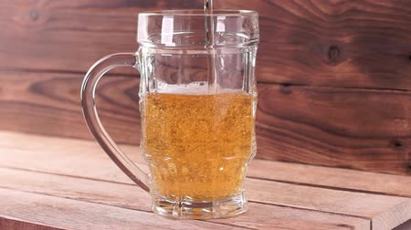 brew : Light beer is poured into a transparent beer mug on a brown wooden background