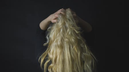 blond vlasy : Woman touching her long curly blonde hair in black background