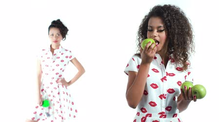 kıvırcık saçlar : Two fashion models posing in studio. Black american model biting an apple and asian model isolated in white background. Fashion shot.