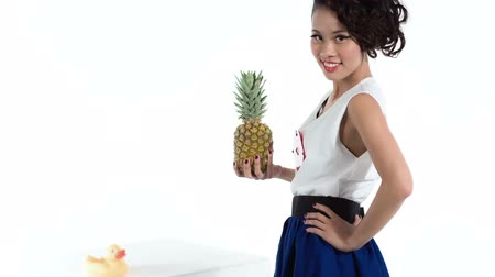 ananász : Cheerful asian woman with pineapple posing in studio. Fashion shot on white background. Pin up style.