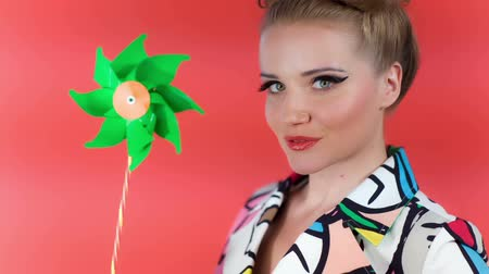 darbe : Beautiful Caucasian Model Holding And Blowing On Green Pinwheel Posing In Front Of Camera. Fashion shot. Pin Up Style. Cheerful Look. Studio Shot On Red Background.