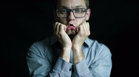sulk : Caucasian attractive man in glasses - bored portrait on black background in studio. Shot on tripod in studio. Black background.
