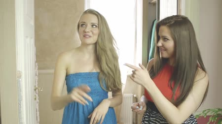 nowe mieszkanie : Beautiful blonde girl showing new dress to her friend at home. Attractive girls talking about fashion.