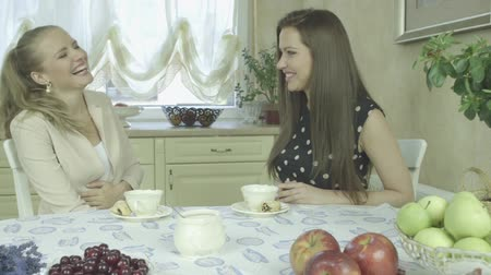 столовая : Two attractive friends talking and having relaxing time at home while drinking tea and eating fresh fruits Стоковые видеозаписи