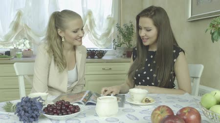 столовая : Two Beautiful Elegant Caucasian friends watching magazine and having tea time at home. Beautiful interior design. Luxuryelegant kitchen.  Стоковые видеозаписи