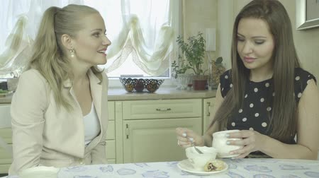 coffee time : Two attractive girlfriends talking while sitting at the dining table in the bright cosy kitchen