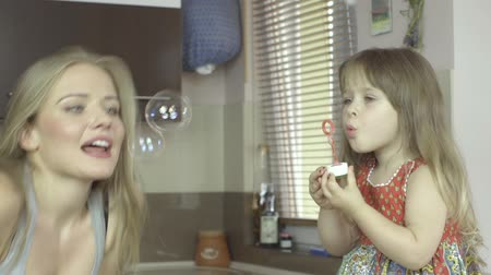 üfleme : Happy mother and daughter blowing bubbles in the kitchen. Portrait of mother and daughter -profile view  Stok Video