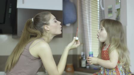 мама :  Happy mother and daughter blowing bubbles in the kitchen.
