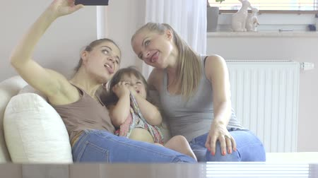 различный : Three sisters at different age making selfie by smartphone at home  Стоковые видеозаписи