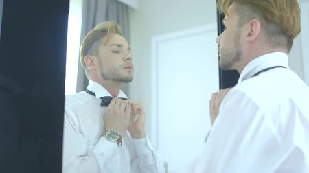 tying : Young man adjusting his bow tie while standing against mirror