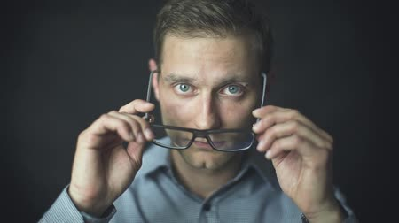 caucasiano : Handsome man in shirt putting on glasses over black background