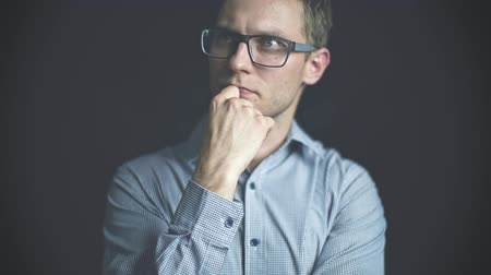 komoly : Close up of pensive man in glasses over black background.