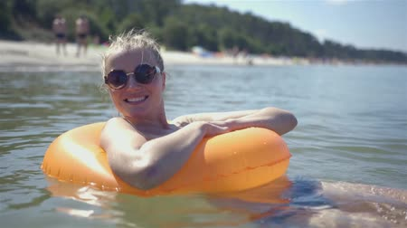 halkalar : Pretty girl floats on a lifebuoy ring in the sea, somewhere in Poland. Stok Video