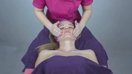 лицевой : Facial massage for beautiful young woman in beauty salon, footage of calm beautiful woman in massage salon