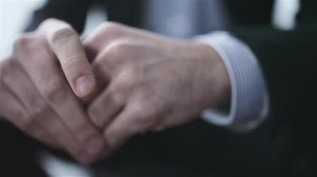 gergin : Waiting businessman with his hands clasped. Close up of hands.