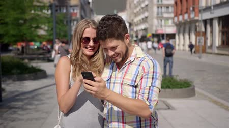 outside : Attractive couple taking self-portrait with phone in a city