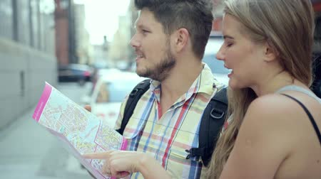 направлять : Young couple with a city map during a sightseeing  Стоковые видеозаписи