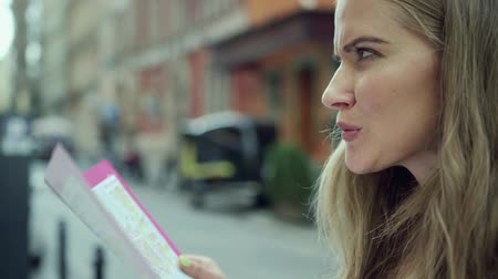 направлять : Beautiful young woman with a city map during sightseeing in a city.  Стоковые видеозаписи