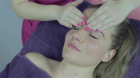 eyes closed : Facial massage for beautiful young woman in beauty salon, footage of calm beautiful woman in massage salon