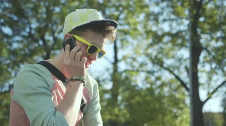 deskorolka : Portrait of a stylish cheerful boy talking on phone, outdoors. Wideo